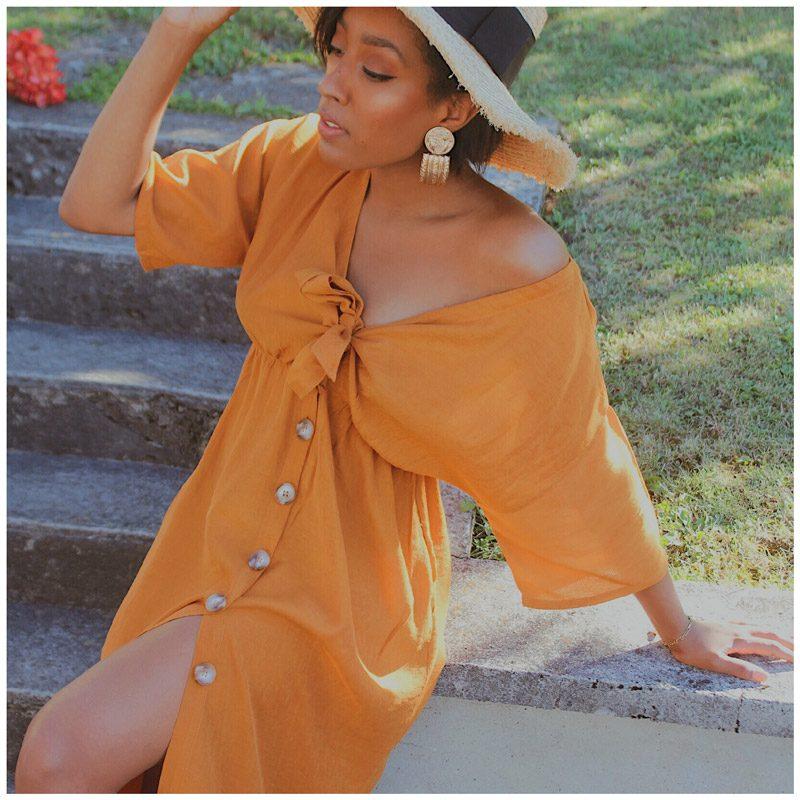 Linda_smt porte la robe sahara ocre. Elle a un noeud ajustable à la poitrine et des boutons sur le devant