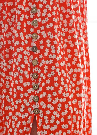 Détails de la jupe rouge à petites fleurs blanches