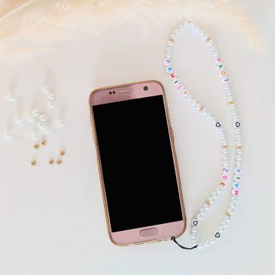 Bijou de téléphone à personnaliser aux prénoms de vos enfants et aux perles blanches nacrées et dorées