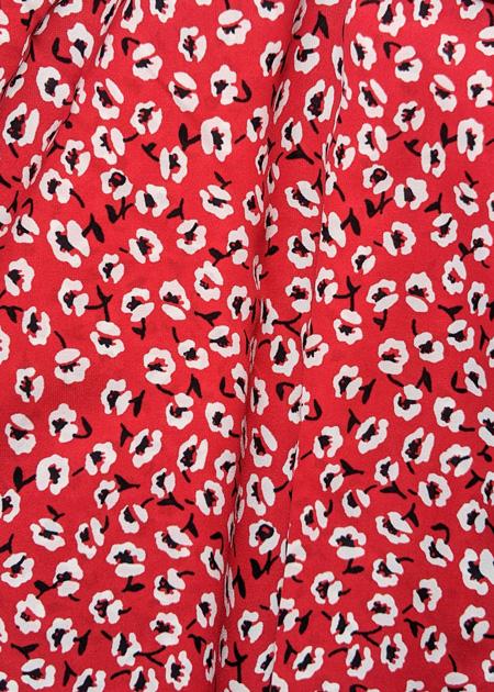 Détails de la jupe longue rouge aux petites fleurs blanches, asymétrique et tendance
